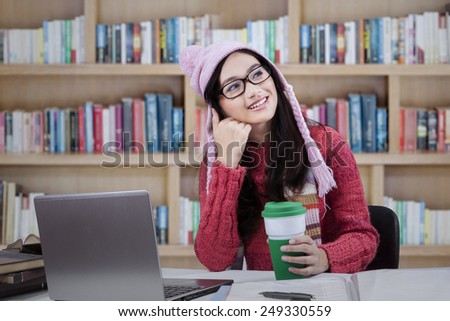 Female student studying in the library while thinking an idea and wearing winter clothes - stock photo