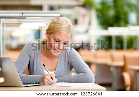Female student studying on the laptop sitting at the desk. Process of studying - stock photo