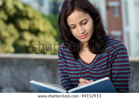 Female student studying outdoors - stock photo