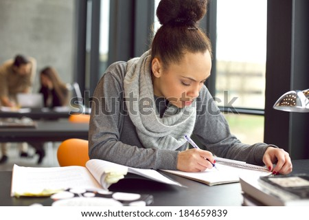 Female student taking notes from books for her study. Young african american woman sitting at table with books for finding information. - stock photo