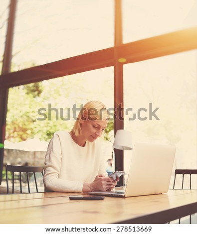 Female student typing text on smart phone sitting at wooden library table with open laptop, young business woman working at modern coffee shop, freelancer use notebook at hipster loft space, flare sun - stock photo