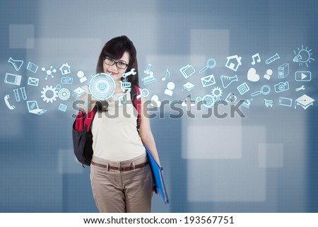Female student using futuristic interface for accessing information - stock photo
