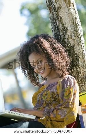 Female student using laptop, outdoors, (portrait) - stock photo