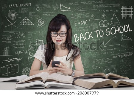 Female student using mobile phone in classroom - stock photo