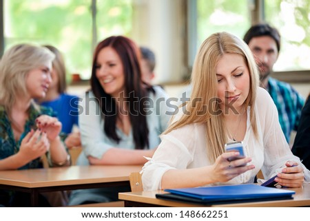 Female student using phone in classroom - stock photo