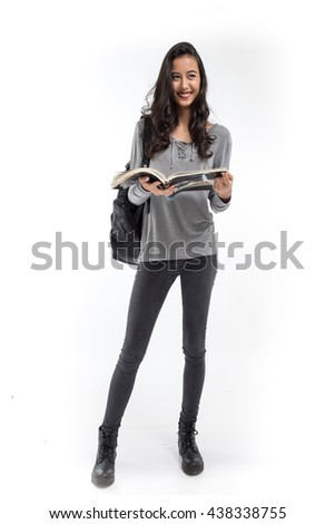 Female student with a backpack holding a book and smiling on white background - stock photo