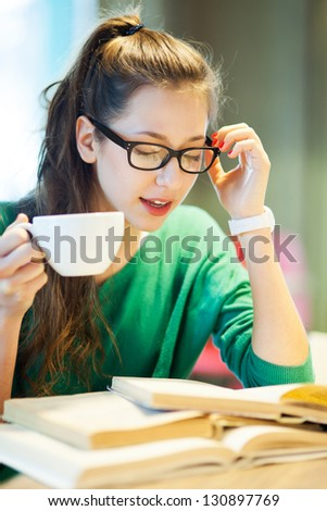 Female student with books and cup of coffee - stock photo