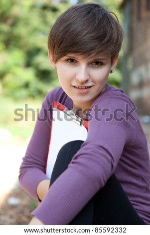 Female student with clipboard sitting near the wall in park - stock photo