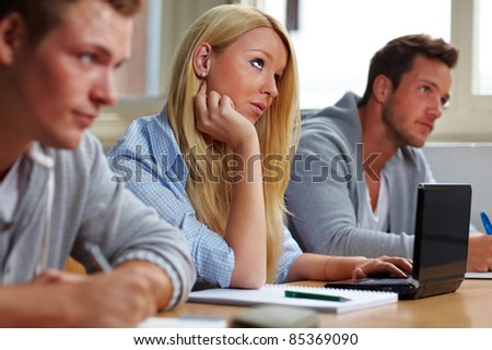 Female student with computer in university class - stock photo