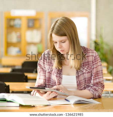 female student with electronic pad in library - stock photo