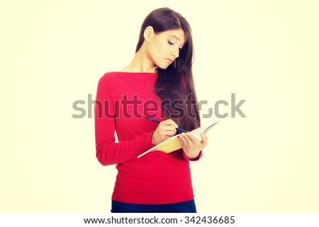 Female student with notebook and pen. - stock photo