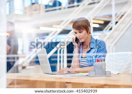 Female student with phone working on laptop in modern space - stock photo