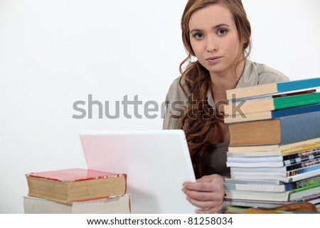 female student with pile of books and laptop - stock photo