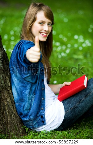 Female student with thumbs up - stock photo