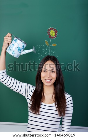 female student with watering can and drawn flower on her head - stock photo