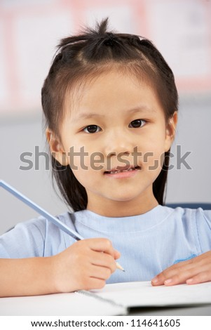 Female Student Working At Desk In Chinese School Classroom - stock photo