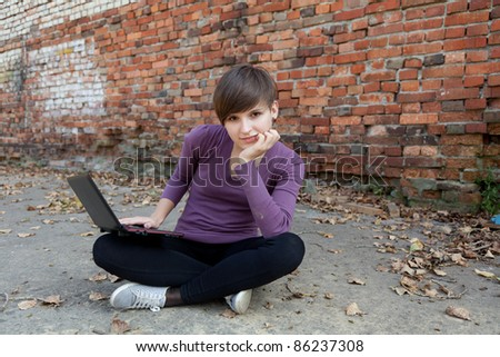 Female student working on laptop near the wall