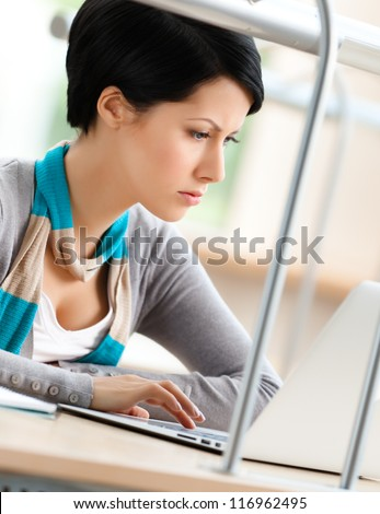 Female student works on the laptop sitting at the desk - stock photo