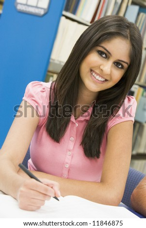 Female student writing report in library - stock photo