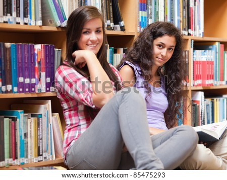 Female students holding a book in a library - stock photo