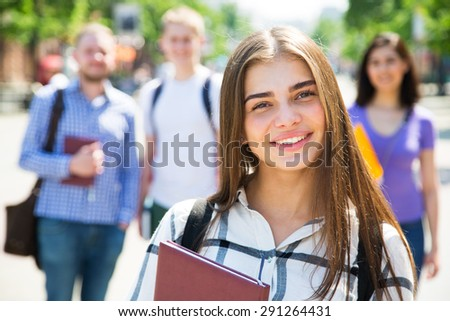 Female students outdoors with her friends - stock photo