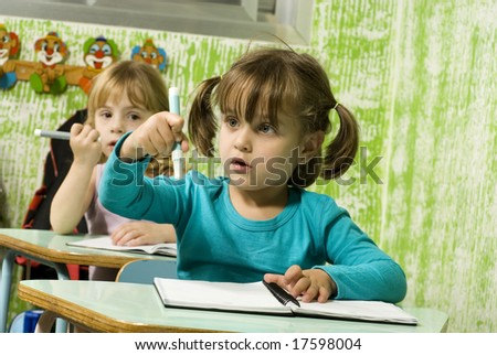 Female students sitting at desks in a classroom.  They are holding pens in their hands.  Horizontally framed shot. - stock photo