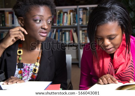 Female Students studying at the College Library - stock photo