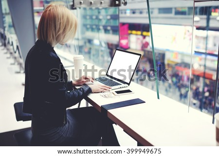 Female successful businesswoman is using for distance work laptop computer with empty copy screen for your advertising text message. Hipster girl is searching information on web page via net-book - stock photo