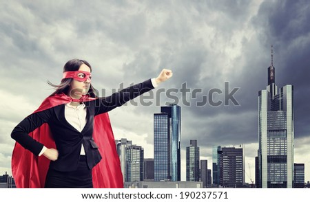 Female superhero standing in front of a dark city  - stock photo