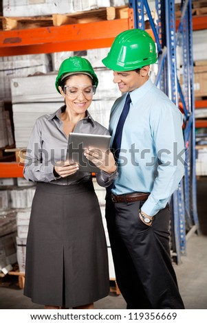 Female supervisor and male colleague using digital tablet at warehouse