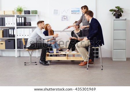 Female supervisor passing around agenda schedules to employees during meeting at small office with storage shelves and white bulletin board in background - stock photo