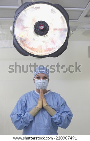 Female surgeon praying in operating room - stock photo