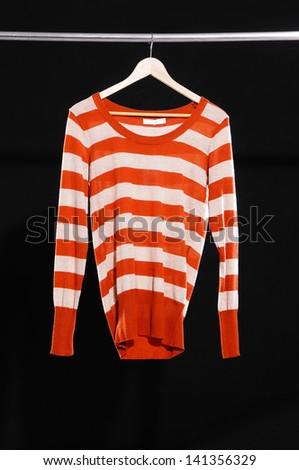 female sweater dress isolated on hanging-black background - stock photo