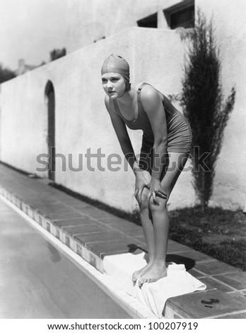 Female swimmer at edge of pool - stock photo
