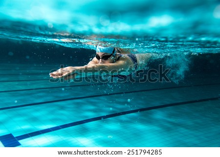 Female swimmer at the swimming pool.Underwater photo. - stock photo