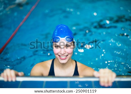 Female swimmer in an indoor swimming pool - doing crawl (shallow DOF) - stock photo