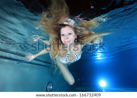 Female swimmer underwater in the pool  - stock photo