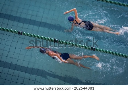 Female swimmers racing in the swimming pool at the leisure center - stock photo
