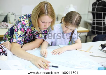 Female tailor teaches student girl how to draw patterns for clothes. Focus on girl. - stock photo