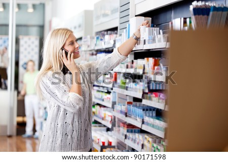 Female talking on cell phone while looking for medicines at drugstore - stock photo