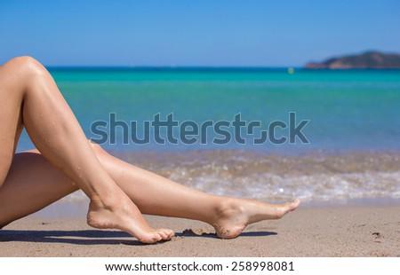 Female tanned slim legs on the white sandy tropical beach - stock photo