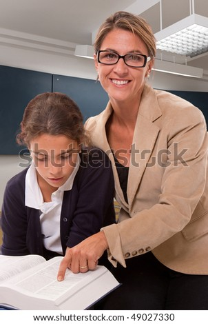 Female teacher and schoolgirl working together in a classroom - stock photo