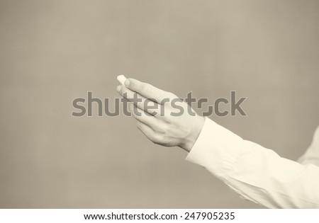 Female teacher hand holding chalk in front of empty blackboard. - stock photo