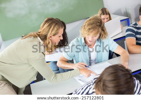 Female teacher helping student in her class - stock photo