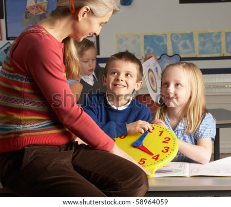 Female Teacher In Primary School Teaching Children To Tell Time In Classroom - stock photo