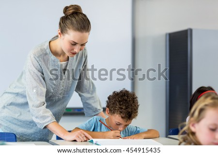 Female teacher looking at student writing on book in classroom - stock photo