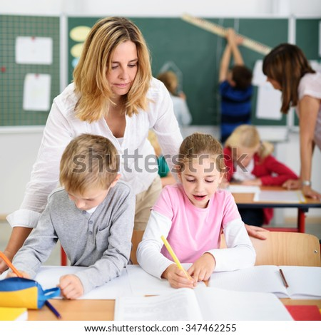 Female Teacher Looking at the Kids While Answering their Exams Inside the Classroom. - stock photo