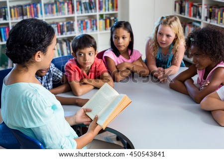 Female teacher reading book at children look at her library