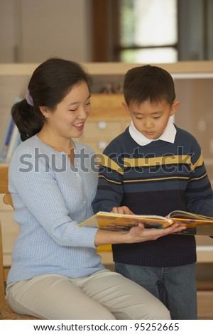 Female teacher reading book with student - stock photo
