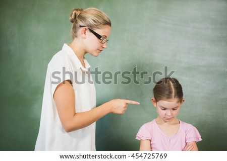 Female teacher shouting at girl in classroom at school - stock photo